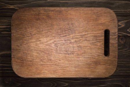 Foto de Vista superior de la tabla de cortar madera en la mesa negra - Imagen libre de derechos