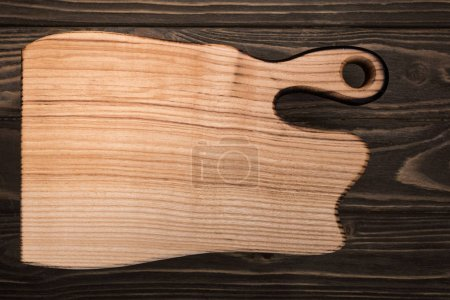 Photo pour Vue supérieure de la planche à découper en bois sur la table brune - image libre de droit