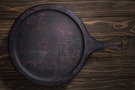 Foto de Vista superior de la tabla de cortar negro en la mesa marrón - Imagen libre de derechos