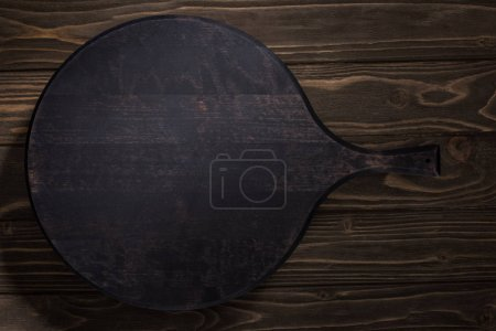 Photo for Top view of black cutting board on brown table - Royalty Free Image