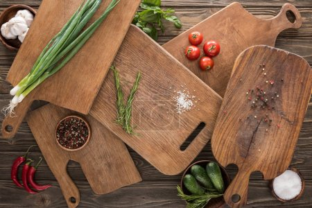Photo for Top view of cutting boards, cherry tomatoes, salt, garlics, cucumbers, chili peppers and spices - Royalty Free Image