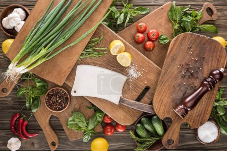 Photo for Top view of cutting boards, cherry tomatoes, salt, garlics, cucumbers, chili peppers, pepper mill, meat chopper, lemons and spices - Royalty Free Image