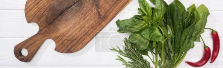 Photo for Panoramic shot of wooden chopping board, chili peppers and greenery - Royalty Free Image