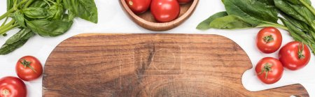 Photo for Panoramic shot of wooden chopping board, greenery and cherry tomatoes - Royalty Free Image