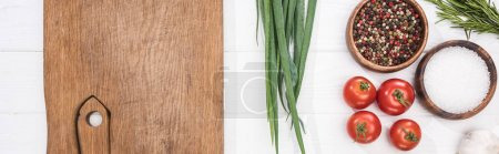 Photo for Panoramic shot of wooden chopping board, garlic, salt, cherry tomatoes, spices and greenery - Royalty Free Image