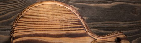 Photo for Panoramic shot of wooden cutting board on brown table - Royalty Free Image