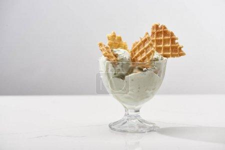 Photo pour Délicieuse crème glacée à la pistache avec des gaufres isolées sur le gris - image libre de droit