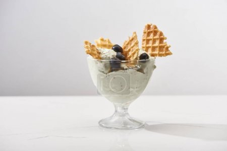 Photo for Delicious pistachio ice cream with waffles and blueberries isolated on grey - Royalty Free Image