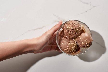 Photo pour Vue partielle de femme retenant la crème glacée délicieuse de chocolat dans le bol sur le fond gris de marbre - image libre de droit