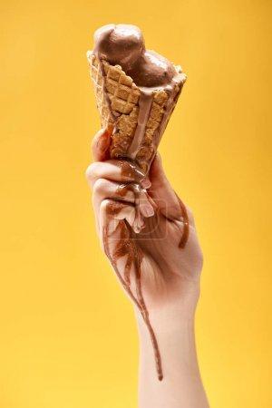 Teilansicht der Frau mit köstlichem geschmolzenem Schokoladeneis in knusprigem Waffelkegel isoliert auf gelb