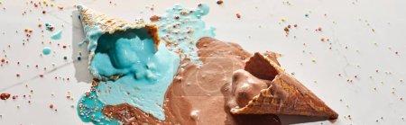 Photo pour Délicieux chocolat fondu et crème glacée bleue dans des cônes de gaufre sur fond gris de marbre avec des arrosages, projectile panoramique - image libre de droit