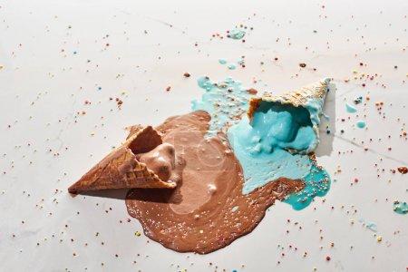 Draufsicht auf köstliche geschmolzene Schokolade und blaues Eis in Waffelkegeln auf marmorgrauem Hintergrund mit Streusel