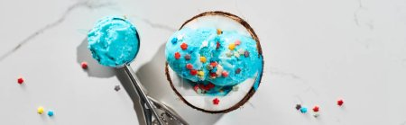 Photo for Top view of delicious blue ice cream with sprinkles on coconut half and in ice cream spoon on marble grey background, panoramic shot - Royalty Free Image