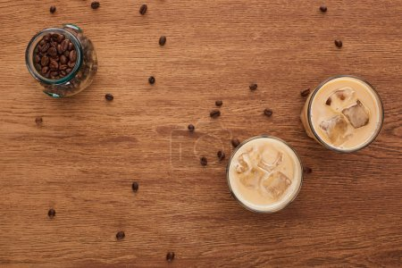 Photo for Top view of ice coffee and coffee grains on wooden table - Royalty Free Image