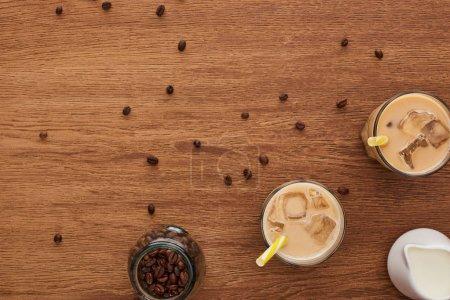 Photo pour Vue supérieure du café de glace dans des glaces avec la paille, le lait et les grains de café sur la table en bois - image libre de droit