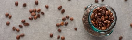 selective focus of coffee grains in glass jar on grey background, panoramic shot