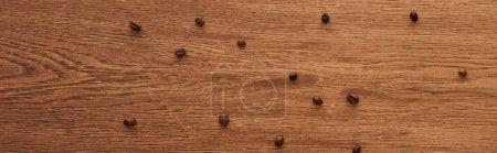Photo pour Vue supérieure des grains de café dispersés sur la table en bois, projectile panoramique - image libre de droit