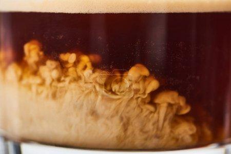Photo pour Vue rapprochée du mélange de café frais avec du lait en verre - image libre de droit