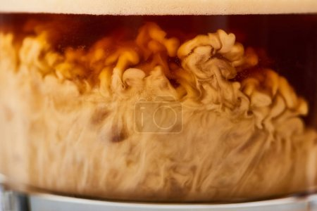 Photo for Close up view of tasty coffee mixing with milk in glass - Royalty Free Image