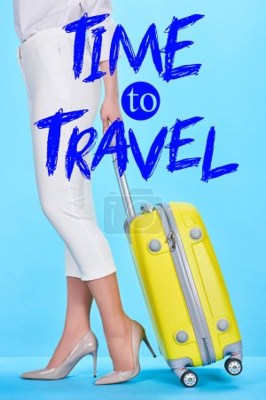 Photo pour Vue recadrée de la femme tenant poignée de sac de voyage jaune sur fond bleu avec le temps de voyager illustration - image libre de droit