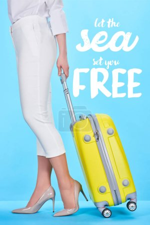 Photo for Cropped view of woman holding handle of yellow travel bag on blue background with let the sea set you free illustration - Royalty Free Image