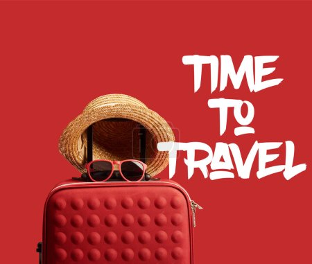 red colorful travel bag with straw hat and sunglasses isolated on red with time to travel illustration