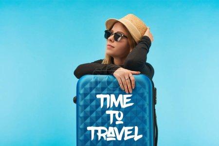 Photo pour Fille blonde en lunettes de soleil et chapeau de paille près de valise bleue avec le temps de voyager illustration isolé sur bleu - image libre de droit