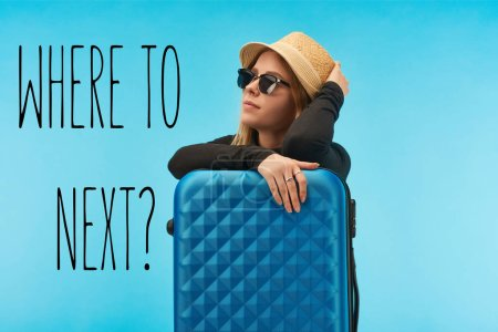 Photo pour Blonde girl in sunglasses and straw hat near blue suitcase isolated on blue with where to next question - image libre de droit