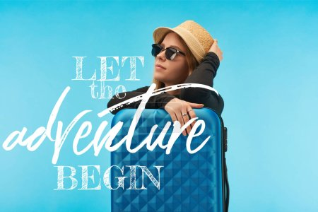 Photo pour Blonde girl in sunglasses and straw hat near blue suitcase isolated on blue with let the adventure begin illustration - image libre de droit