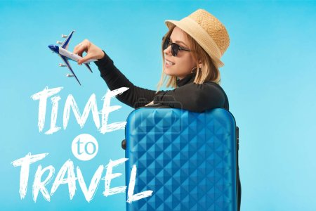 Photo for Blonde happy girl in sunglasses and straw hat plating with toy plane near blue travel bag isolated on blue with time to travel illustration - Royalty Free Image