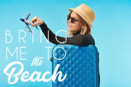 blonde happy girl in sunglasses and straw hat plating with toy plane near blue travel bag isolated on blue with bring me to the beach illustration