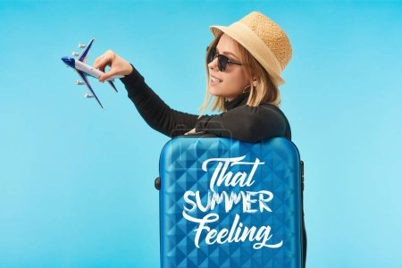 Photo for Blonde happy girl in sunglasses and straw hat plating with toy plane near blue travel bag with that summer feeling lettering isolated on blue - Royalty Free Image