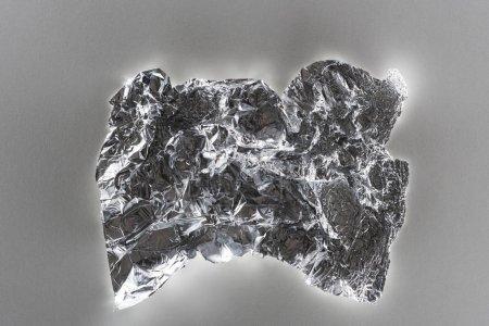 Photo pour Vue supérieure du papier d'argent froissé brillant sur le fond gris - image libre de droit