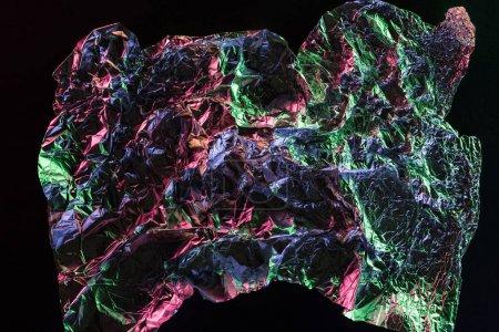 Photo pour Vue supérieure du papier d'aluminium froissé avec la réflexion colorée dans l'obscurité d'isolement sur le noir - image libre de droit