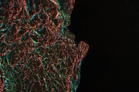 Draufsicht auf glänzende zerknüllte Folie mit farbenfroher Lichtreflexion in der Dunkelheit isoliert auf schwarz mit Kopierraum