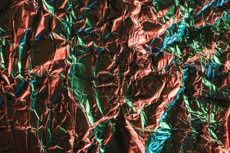 top view of glossy crumpled foil with colorful lighting reflection