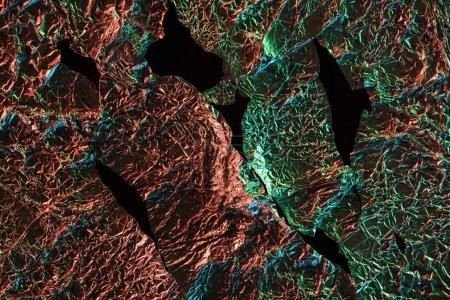 Foto de Vista superior de papel de aluminio arrugado roto con reflejo de iluminación colorido en la oscuridad aislada en negro - Imagen libre de derechos
