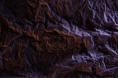 Photo pour Vue supérieure du papier froissé avec l'éclairage coloré pourpre dans l'obscurité - image libre de droit