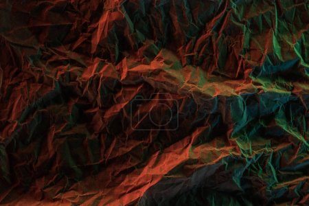 Photo for Top view of crumpled paper with colorful lighting in darkness - Royalty Free Image