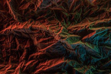 Foto de Vista superior del papel arrugado con iluminación colorida en la oscuridad - Imagen libre de derechos