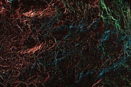 Foto de Vista superior de la lámina arrugada de plata con iluminación colorida en la oscuridad - Imagen libre de derechos