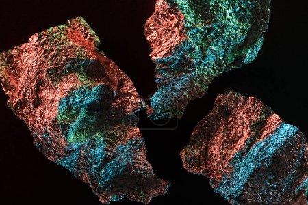 Photo pour Fond abstrait de pièces de papier d'aluminium froissé texturé argent avec éclairage coloré isolé sur noir - image libre de droit