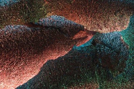 Foto de Fondo abstracto de papel de aluminio desigual texturizado brillante con iluminación colorida - Imagen libre de derechos