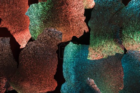 abstract background of ragged foil with colorful illumination isolated on black