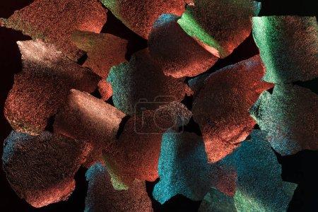 Photo pour Fond abstrait du papier d'argent en lambeaux avec l'illumination colorée d'isolement sur le noir - image libre de droit
