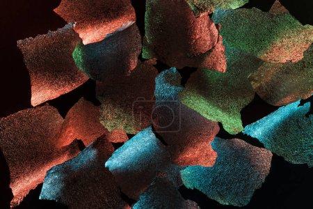 Photo pour Fond abstrait de papier d'argent déchiré texturé avec éclairage coloré isolé sur noir - image libre de droit