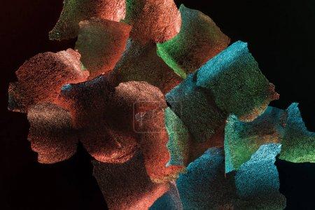 Photo pour Fond abstrait de morceaux de papier d'aluminium texturé avec éclairage coloré isolé sur noir - image libre de droit