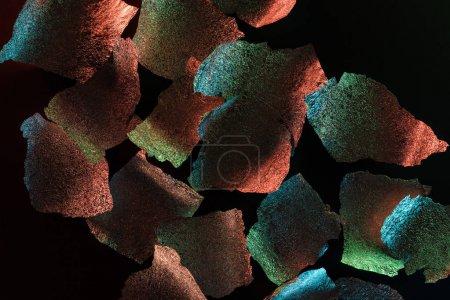 Photo pour Fond abstrait des morceaux argentés de feuille avec l'illumination colorée d'isolement sur le noir - image libre de droit