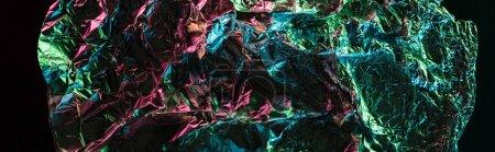 Photo pour Coup panoramique de papier d'aluminium froissé brillant avec le reflet coloré d'éclairage dans l'obscurité d'isolement sur le noir - image libre de droit