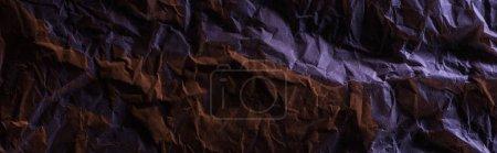 Photo pour Plan panoramique de papier froissé avec un éclairage mauve coloré dans l'obscurité - image libre de droit